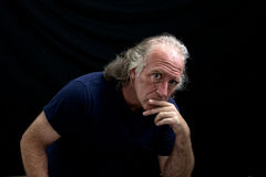 Rugged looking man staring at viewer. Portrait of a rugged looking man turned towards the viewer and looking thoughful or judging with his hand to his mouth Stock Photography