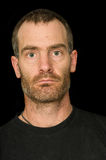 Rugged Man Portrait. Portrait of a rugged grizzled middle aged man with black t-shirt on black background Stock Photo