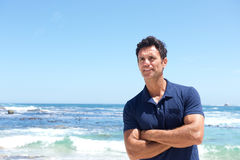 Rugged middle aged man standing at the beach. Portrait of rugged middle aged man standing at the beach Stock Photos