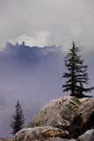 Rugged Mountain Tops. Rugged ridgeline obscured by clouds, framed by trees and granite Royalty Free Stock Photos