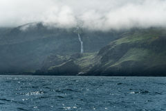 Rugged North Icelandic Coast. Between sea and fog with a waterfall Royalty Free Stock Photos