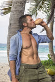 Rugged outdoorsman drinking coconut water Royalty Free Stock Images