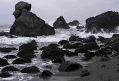 Rugged Pacific Coast in California. Overcast sky and black rocks in the surf Royalty Free Stock Photos