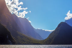 Rugged  peaks of Milford Sound with sun rays. Fiordland, New Zea Royalty Free Stock Image