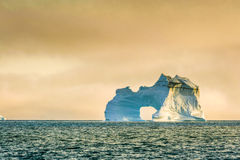A rugged and powerful iceberg sits alone in the Arctic ocean. A dirty, weather worn ice berg shows the ravages of time as it floats alone in the ocean royalty free stock photography