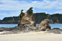 Rugged rock formation on sandy beach Stock Image
