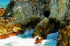 Rugged rocks & caves of tropical island cliff Stock Images