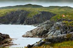 Rugged rocky coastal landscape Newfoundland Canada. Maple Leaf Canadian Flag pole alone in barren coastal landscape of Newfoundland, NL, Canada royalty free stock photo