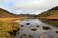 The rugged, rocky landscape of Llyn Mymbyr and Capel Curig. The rocks and reeds strewn across the calm waters entering Llyn Mymbyr lake and the surrounding Royalty Free Stock Photos