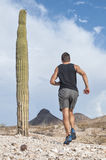 Rugged run. Muscular Caucasian male runner in shorts and running shoes runs across rugged rocky desert terrain Royalty Free Stock Images