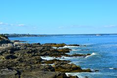 Rugged shoreline of the Casco Bay. At the entrance to the harbor at Portland, Maine ; Hog Island and Portland in the far background Royalty Free Stock Image