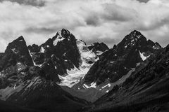 Rugged Snowy Mountain Range. Jagged mountain tops reach into heavy clouds in the sky. Snow and a glacier makes its way into the valley below Stock Photo