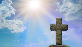 Symoblic Cross of Jesus Christ and God`s Light. Rugged stone cross in foreground with a bright blue sky and stuffing sun burst shining down providing copy space Royalty Free Stock Photo