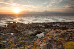 Rugged sunset coastline lit up by the evening sunbeams. The rugged coastline of Somerset lit up by the gorgeous setting sun Royalty Free Stock Images