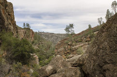Rugged Western Mountain Landscape. A panoramic outdoor vista view of a rugged western landscape and canyon with the surrounding mountains along a trail in Royalty Free Stock Photos