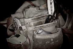 Rugged worn leather carpenters work bags with construction tools Royalty Free Stock Photo