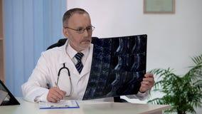 Ruggegraatschirurg die backbonemri onderzoeken, die nota's in patiëntenmedisch dossier maken stock afbeelding
