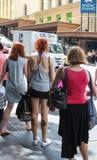 Ruggen van vrouwenklanten met al hun zakken die op het zebrapad in dichtbijgelegen Anzac Square wachten stock afbeelding