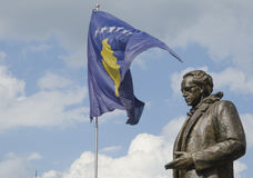 Rugova staty med den Kosovo flaggan i Pristina Arkivbild