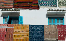 Rugs on Whitewashed building. Colorful Mats on Balcony of North African House Stock Images