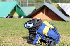 Rugzak amid de tenten van kamp tijdens de avontuurlijke excursie Stock Afbeeldingen