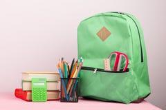 rugzak en schoollevering: de blocnote, boeken, schaar, pennen, potloden, heerser, calculator is op een roze houten lijst stock fotografie