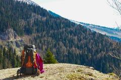 Rugzak en trekkingspool op een achtergrond van bergen die op een bergklip rusten Stock Afbeelding