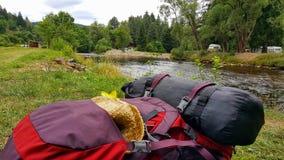Rugzak op de bank van Otava-Rivier stock afbeeldingen