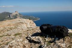 Rugzak op piek van berg met overzees en bergen op achtergrond, gezond lifestile en wandelingsconcept Royalty-vrije Stock Afbeeldingen