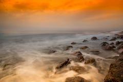 Ruhe bewegt unter einen orange Himmel wellenartig Stockbilder