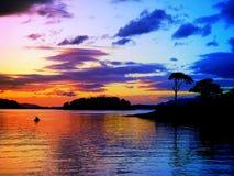 Ruhe und Frieden bei einem macht-vollen Farbe-vollen Sonnenuntergang mit Kanu Stockfoto