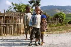 RUHENGERI, RWANDA - SEPTEMBER 7, 2015: Onbekende kinderen De jonge geitjes die samen koesteren en de andere jonge geitjes achter  Royalty-vrije Stock Foto