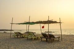 Ruhesessel eines leere alte hölzerne Strandes unter einer Palmenüberdachung auf dem sandigen Strand des Ozeans am Abend rote Fahn stockbild