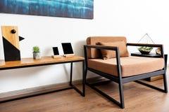 Ruhesessel mit Schreibtisch und kleinem Kabinett in der hellen Wohnung Lizenzfreie Stockfotos
