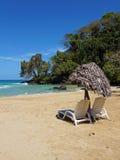 Ruhesessel mit Sonnenschirm auf einem tropischen Strand Stockfotos
