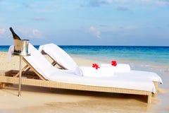 Ruhesessel am Rand von tropischem Meer mit Champagne Bucket Lizenzfreie Stockbilder