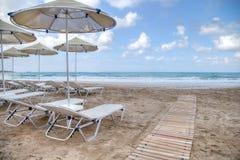 Ruhesessel und Strandschirme auf einem sandigen Strand Lizenzfreie Stockfotos