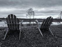 Ruhestand und zwei Stühle, die den Sonnenuntergang im Sumpf betrachten Stockbild