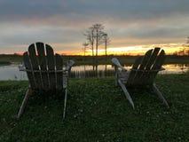 Ruhestand und zwei Stühle, die den Sonnenuntergang im Sumpf betrachten Stockfotografie