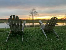 Ruhestand und zwei Stühle, die den Sonnenuntergang im Sumpf betrachten Lizenzfreies Stockbild