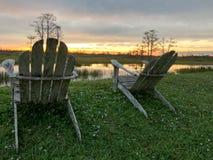 Ruhestand und zwei Stühle, die den Sonnenuntergang im Sumpf betrachten Lizenzfreies Stockfoto