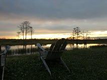 Ruhestand und zwei Stühle, die den Sonnenuntergang im Sumpf betrachten Stockfoto