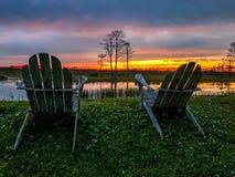 Ruhestand und zwei Stühle, die den Sonnenuntergang im Sumpf betrachten Lizenzfreie Stockfotografie