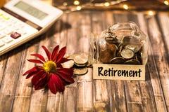 Ruhestandsgeldglas-Einsparungens-Motivkonzept auf hölzernem Brett Lizenzfreies Stockfoto
