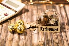 Ruhestandsgeldglas-Einsparungens-Motivkonzept auf hölzernem Brett Stockbild