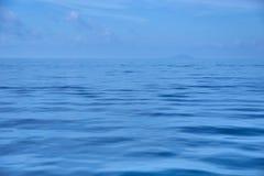 Ruhig vom Ozean mit einsamem blauem Himmel stockbild