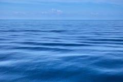 Ruhig vom Ozean mit einsamem blauem Himmel lizenzfreie stockbilder