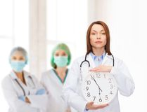 Ruhige Ärztin mit Wanduhr Lizenzfreie Stockbilder