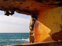 Ruhige Ansicht von Sommermeereswogen des blauen Wassers durch abgefressene Steinlochbildung in den orange warmen Farben lizenzfreies stockfoto