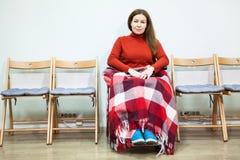 Ruhige behinderte Frau im Rollstuhl mit Decke auf den Beinen, die Kamera beim Sitzen im Raum betrachten Stockfoto